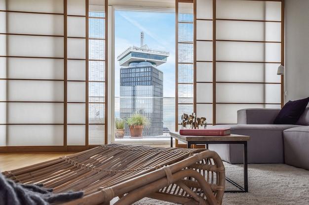 Sala de estar moderna con muebles cómodos y vista del edificio de gran altura en la ciudad