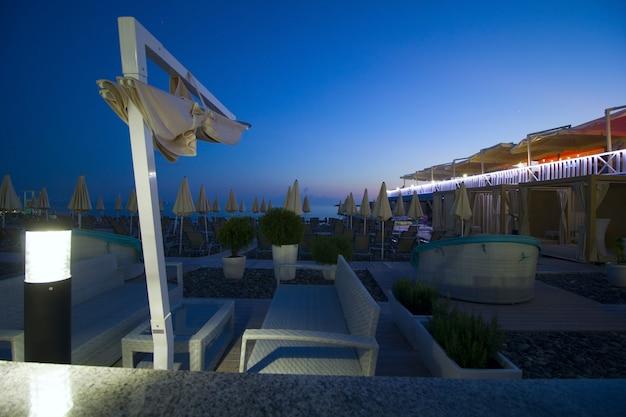Sala de estar en la playa hamacas sombrillas en la noche al atardecer