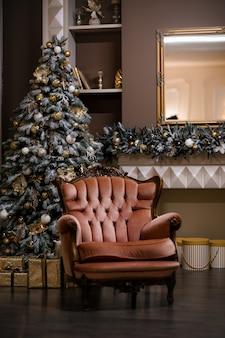 Sala de estar con sillón color beige, árbol de navidad y regalos. interior de navidad