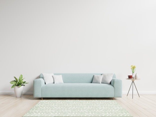 Sala de estar con sofá con almohadas, planta y florero con flores sobre fondo de pared blanca
