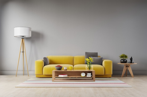 Sala de estar con sofá amarillo de tela, sillón amarillo, lámpara y planta verde en florero en pared oscura.