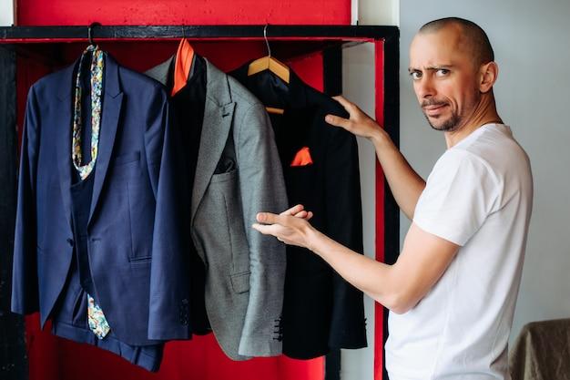 En una sala de exposición de ropa para hombres, un chico elige un traje para una entrevista