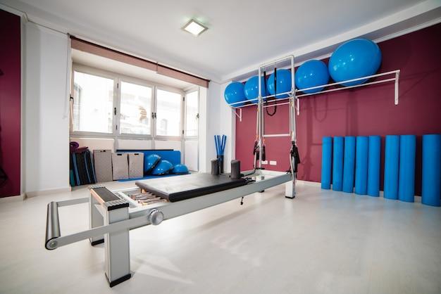 Sala de gimnasia vacía con equipos modernos para el entrenamiento de pilates