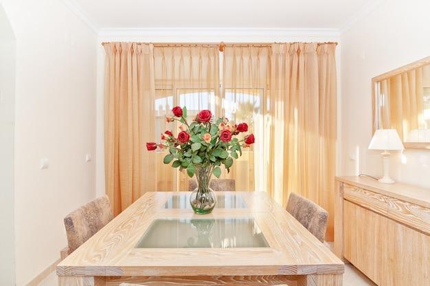 La sala de un hermoso ramo de rosas rojas en un jarrón. en la mesa.