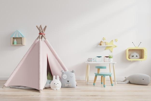 Sala de juegos para niños con carpa y mesa sentado detrás de la pared blanca.