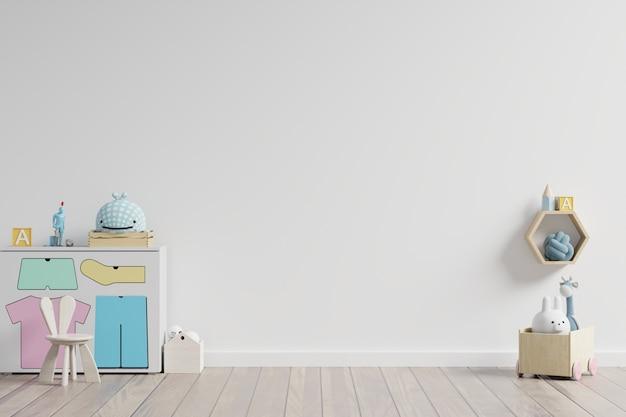 En la sala de juegos para niños con gabinete y mesa sentado muñeca en la pared blanca vacía.