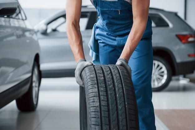 Sala limpia. mecánico sosteniendo un neumático en el taller de reparación. reemplazo de neumáticos de invierno y verano.
