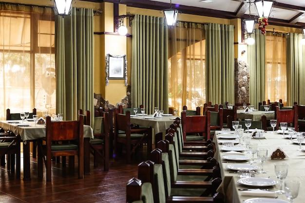 Sala de restaurante de estilo clásico con sillas y cortinas de madera verde.