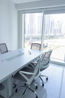 Sala de reuniones con magníficas vistas desde la ventana. sillas de oficina y mesa de conferencias en la oficina. concepto de trabajo de oficina o negocio.