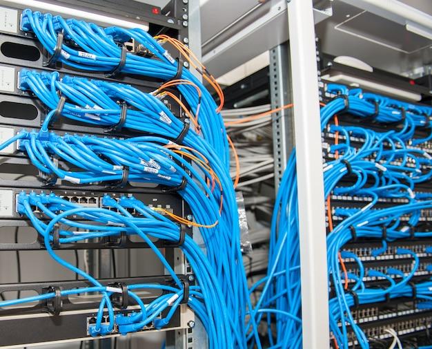 Sala de servidores con enrutadores y cables.