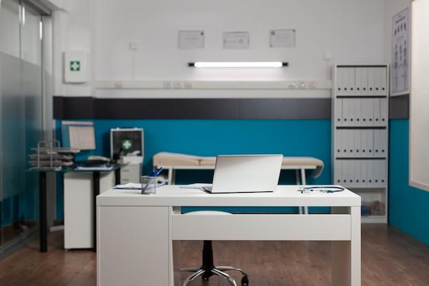Sala de trabajo de médicos vacía con escritorio y tecnología