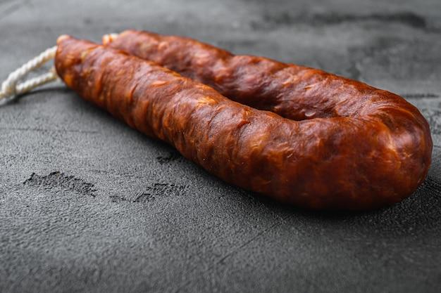 Salami de chorizo de salchicha tradicional sobre fondo de textura gris.