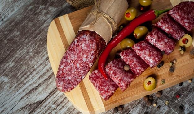 Salami italiano con aceitunas y especias sobre fondo de madera
