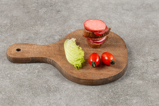Salami en rodajas con pan de centeno y tomate sobre tabla de madera.