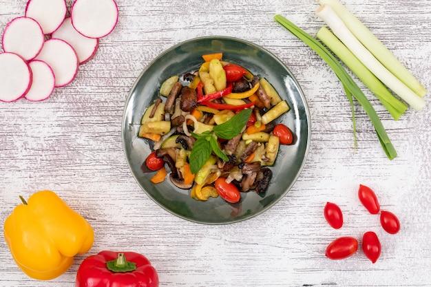 Salat de verduras fritas setas pimiento rojo tomate cherry zanahoria pimiento amarillo en la placa negra sobre superficie de madera blanca