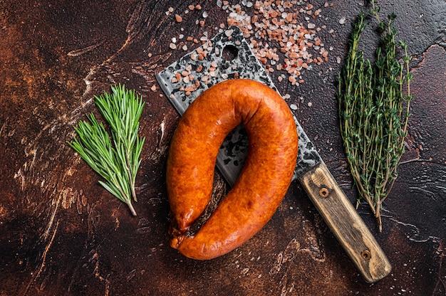 Salchicha ahumada caliente en una cuchilla rústica de carnicero con hierbas. fondo oscuro. vista superior.