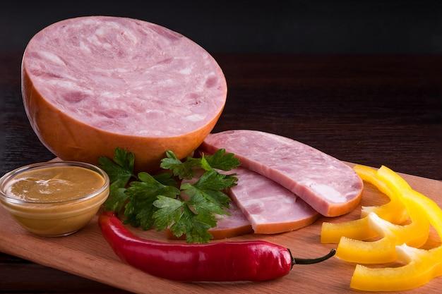 Salchicha con aperitivos en un plato y en una tabla de cortar.