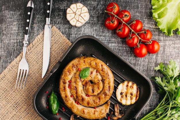 Salchicha de caracol a la plancha en una sartén con verduras frescas
