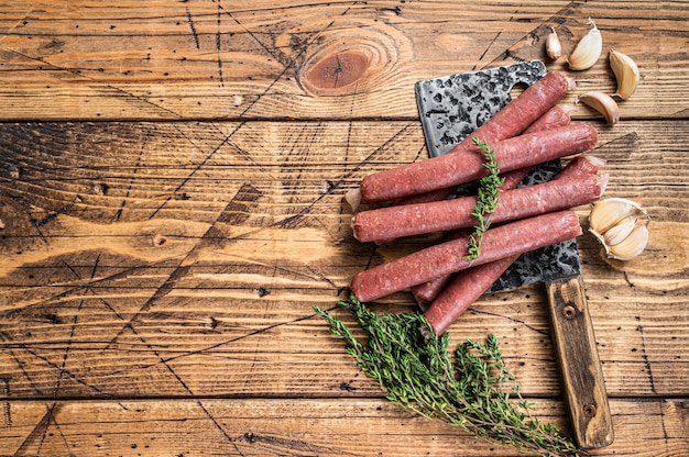 Salchicha cruda de ternera y cerdo cruda en cuchillo de carnicero vintage. fondo de madera.