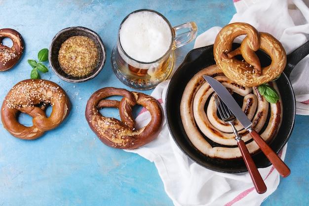 Salchicha frita con cerveza y pretzels.