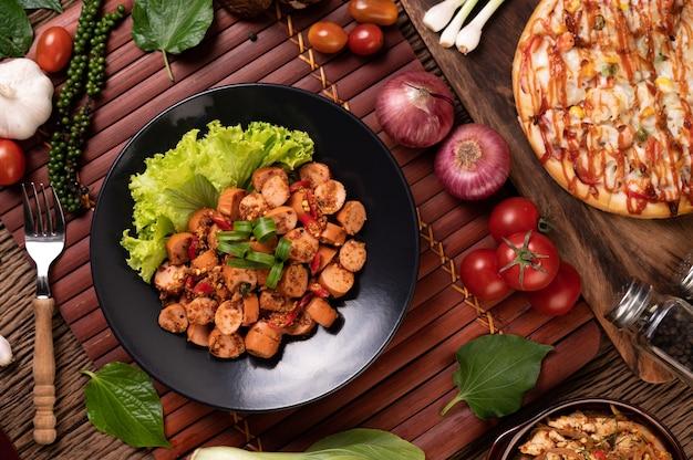 Salchicha larb con chili cebolletas y lechuga en placa negra