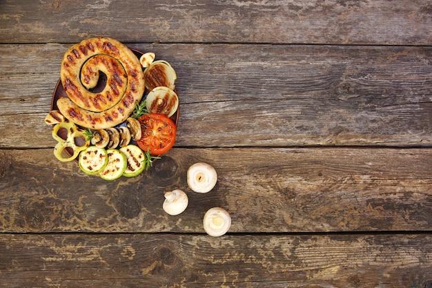 Salchicha a la parrilla y verduras sobre fondo de madera vieja. vista superior. endecha plana.