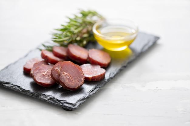 Salchicha portuguesa ahumada con aceite de oliva y romero en pizarra