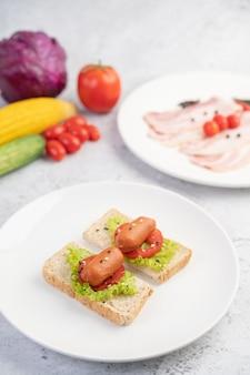 Salchicha con tomate, ensalada y dos juegos de pan en un plato blanco.