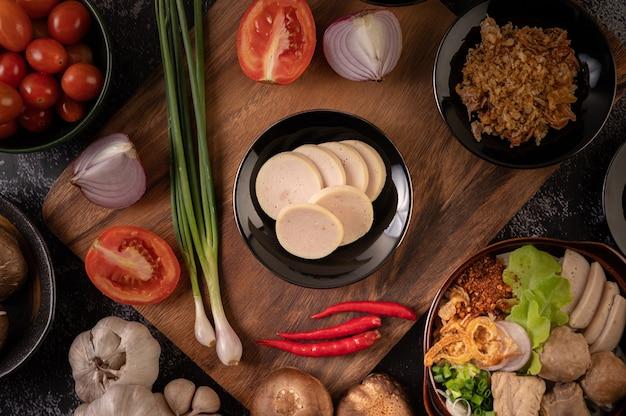 Salchicha vietnamita en un plato con cebolleta, ají, ajo y setas shiitake en un plato de madera.