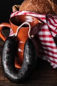 Salchicha y jarra junto a la canasta con pan