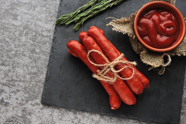Salchichas ahumadas con salsa y romero. vista superior.
