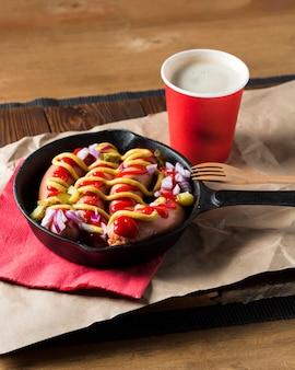Salchichas de alto ángulo en sartén con salsas y cebolla