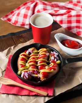 Salchichas de alto ángulo en sartén con salsas