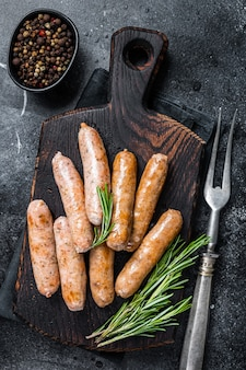 Salchichas bratwurst o hot dogs en una tabla de madera. fondo negro. vista superior.