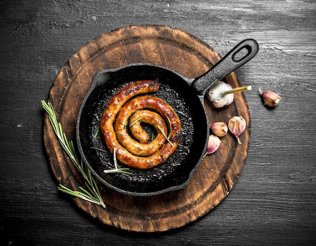 Salchichas calientes en una sartén en la pizarra negra