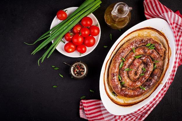 Salchichas caseras de carne en una fuente para horno con cebollas verdes y tomates