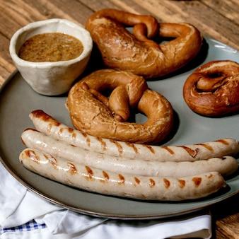 Salchichas de cerdo asadas tradicionales bávaras en plato de cerámica servidas con mostaza dulce alemana, jarra de cerveza oscura y pan de pretzels en una servilleta blanca y azul sobre fondo de madera. imagen cuadrada