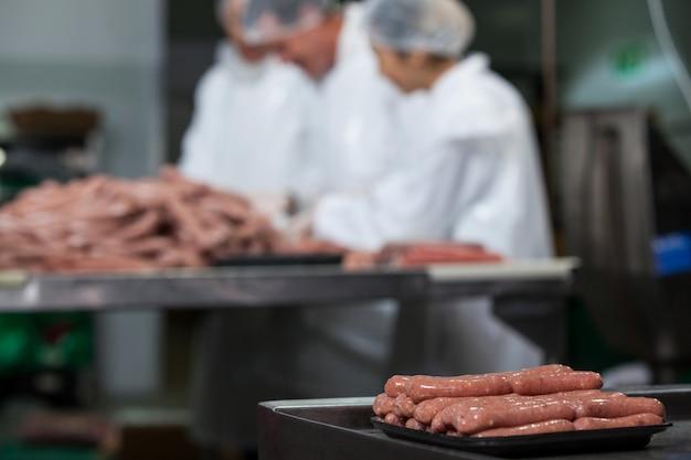 Salchichas crudas dispuestas en bandeja en fábrica de carne