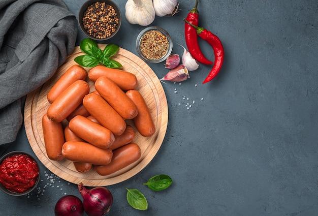 Salchichas crudas, especias y verduras en una tabla para cortar. vista superior, comida rápida.