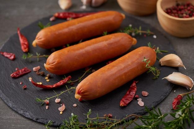Salchichas crudas frescas e ingredientes para cocinar. salchichas de cerdo de carne hervida clásica sobre tabla de cortar con pimienta, romero, hierbas y especias.