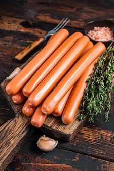 Salchichas frankfurter sobre tabla para cortar madera