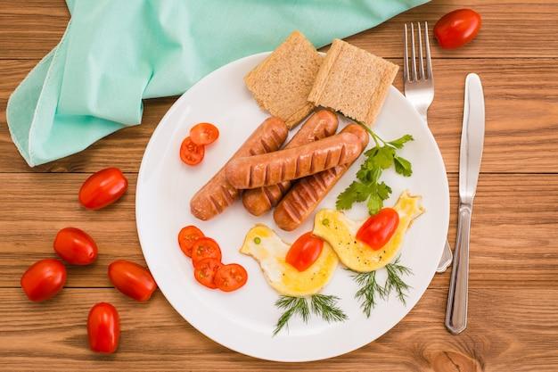 Salchichas fritas, huevos revueltos, tomates cherry y pan, vista superior