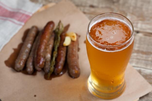 Salchichas fritas y jarra de cerveza fría.