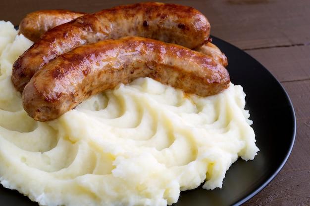 Salchichas inglesas con puré de patatas y salsa.