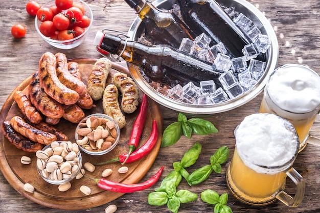 Salchichas a la parrilla con aperitivos y jarras de cerveza.