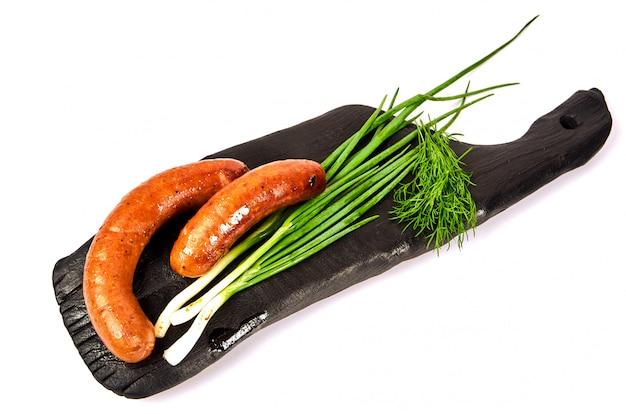 Salchichas a la parrilla eneldo cebolla en un tablero en una luz. jugoso dos anillos de salchichas con verduras en un montón sobre un fondo blanco.