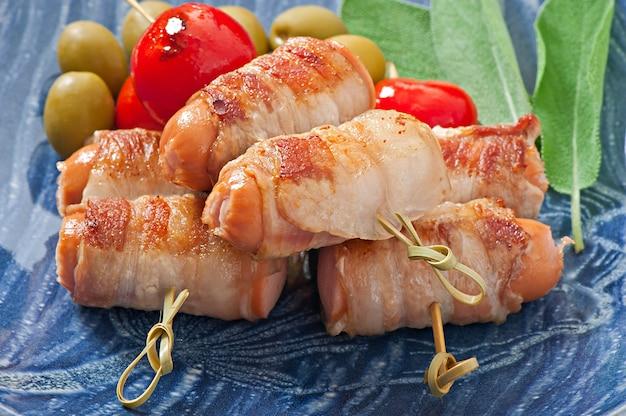 Salchichas a la parrilla envueltas en tiras de tocino con tomates y hojas de salvia