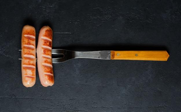 Salchichas a la parrilla fritas en un tenedor de metal.
