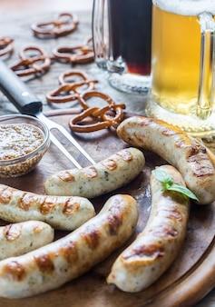 Salchichas a la parrilla con pretzels y jarras de cerveza