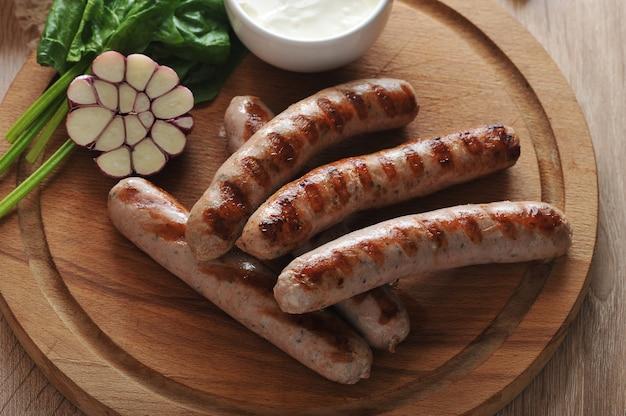 Salchichas a la parrilla con salsa, espinacas y ajo